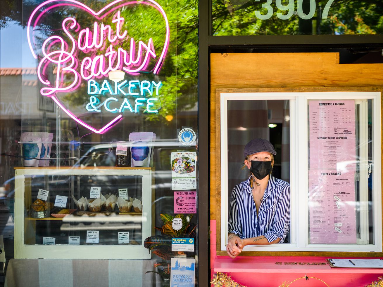 A woman wearing a mask and a hat stands behind a window built into the door at St. Beatrix in Northeast Portland, Oregon.