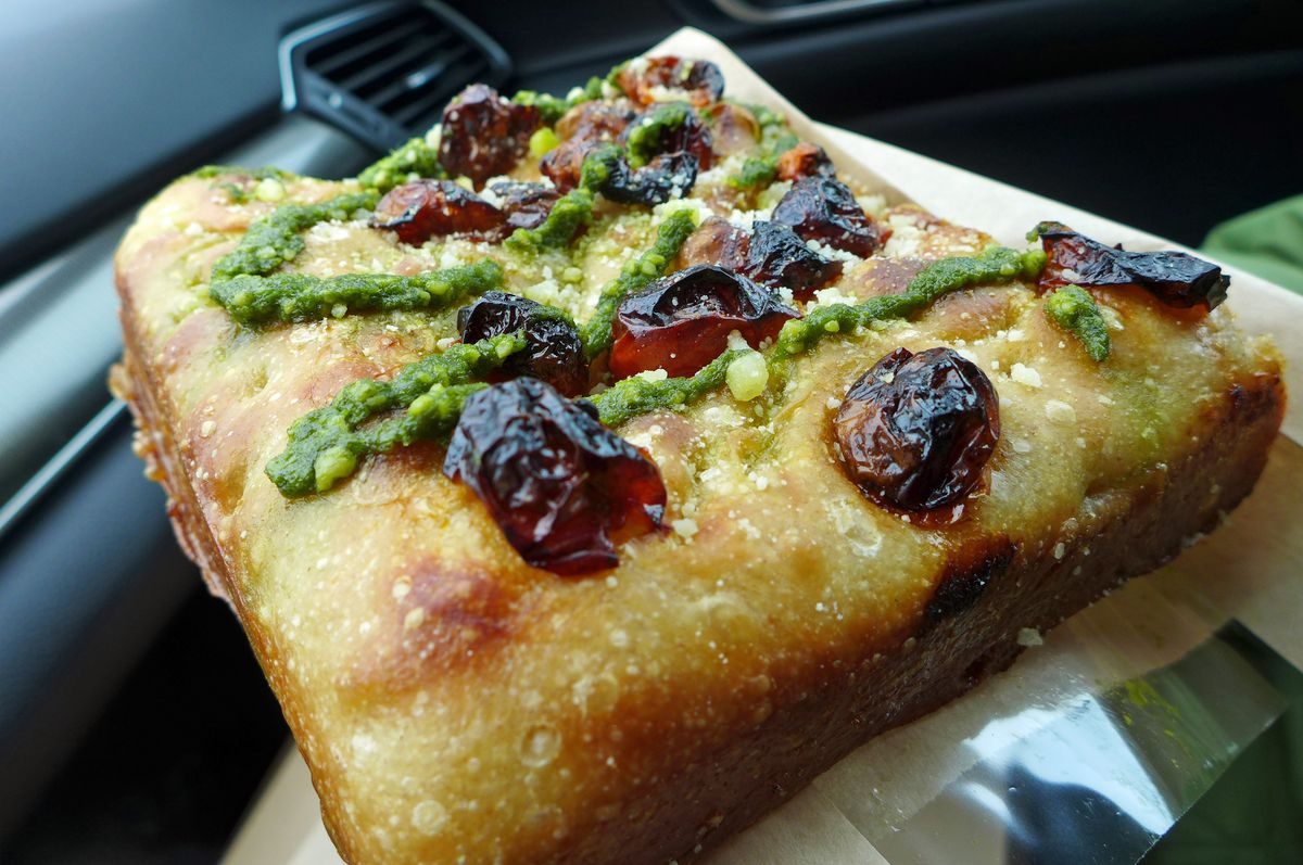 Seen inside a car, a big square of pizza with cheese, green sauce, and charred cherry tomatoes inset on top.