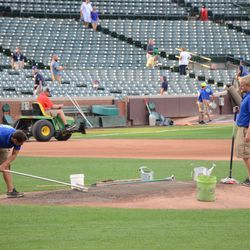 6:23 p.m. The grounds crew working the pitcher's mound -