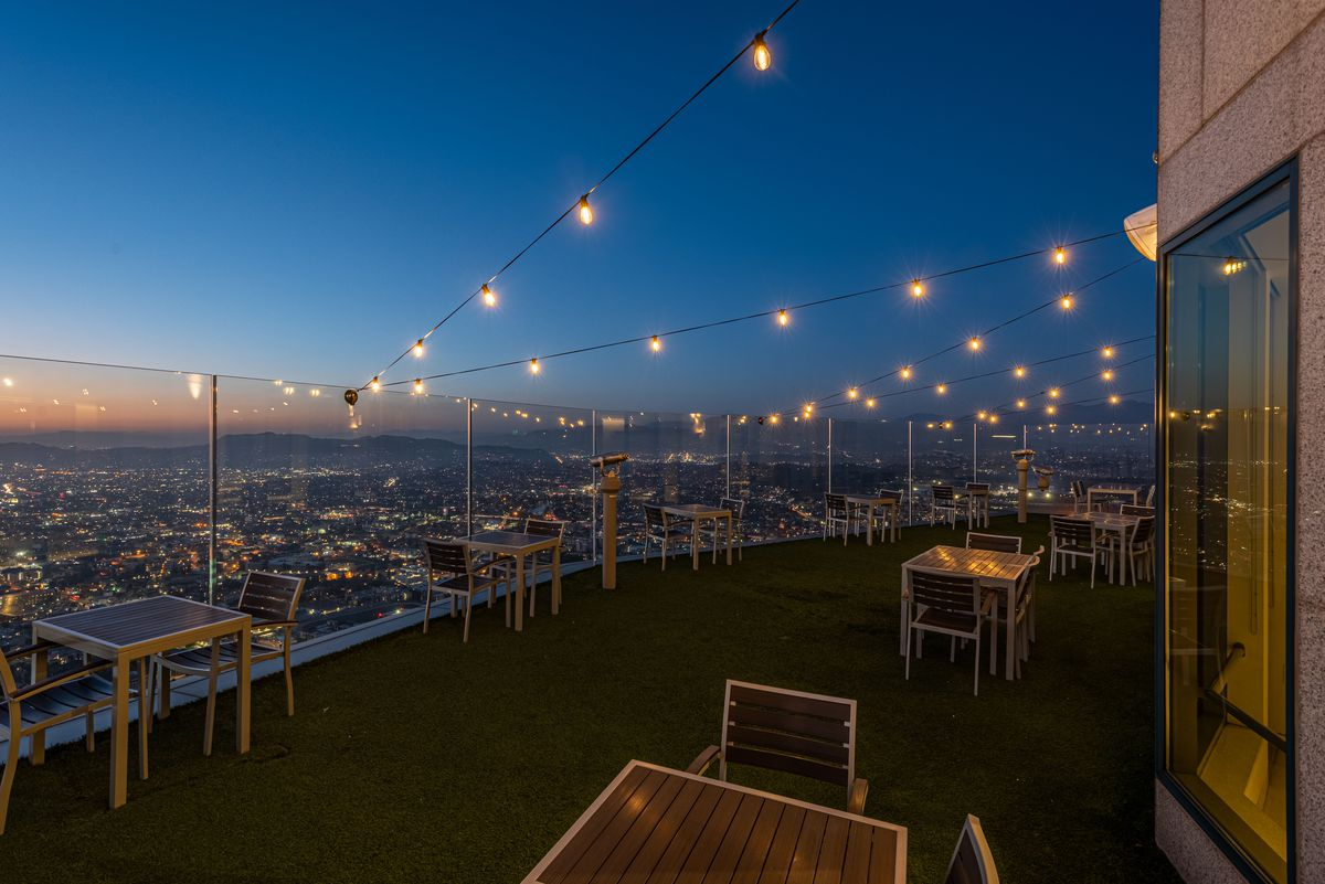Faux green grass and distanced tables at a sky high patio.