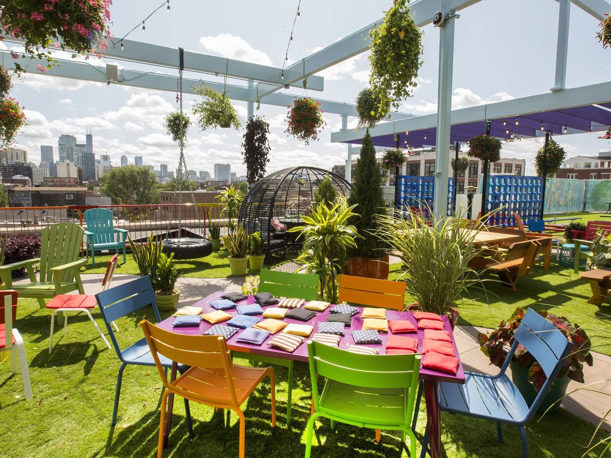 A large, colorful rooftop bar patio with astroturf.