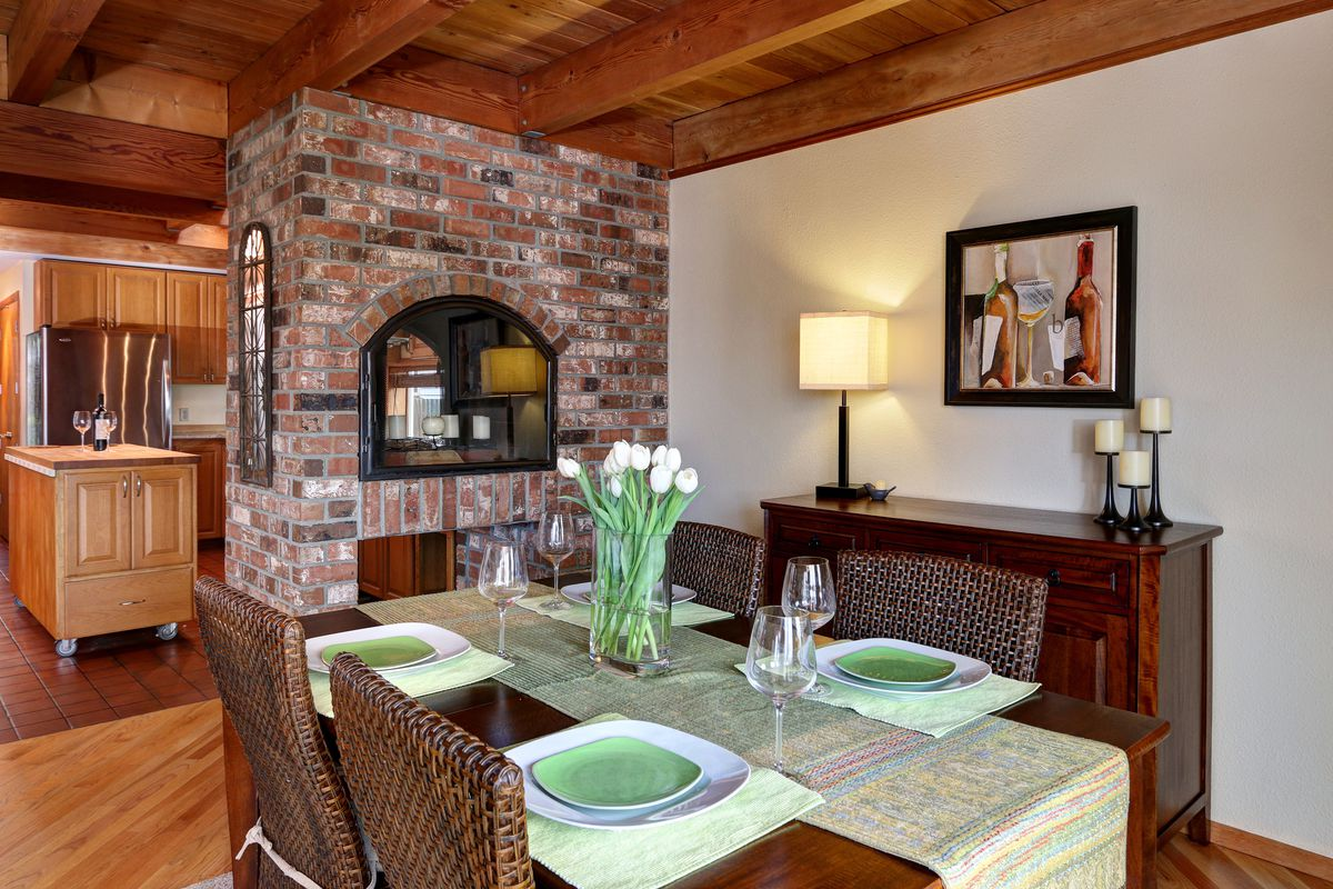 A dining area with a see-through fireplace in a small brick dividing wall leading into the kitchen.