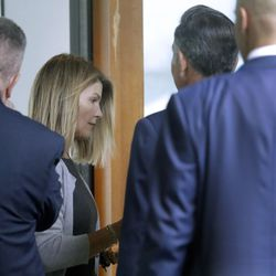 Lori Loughlin, second from left, and her husband Mossimo Giannulli, second from right, enter the back door at federal court Tuesday, Aug. 27, 2019, in Boston, for a hearing in a nationwide college admissions bribery scandal.