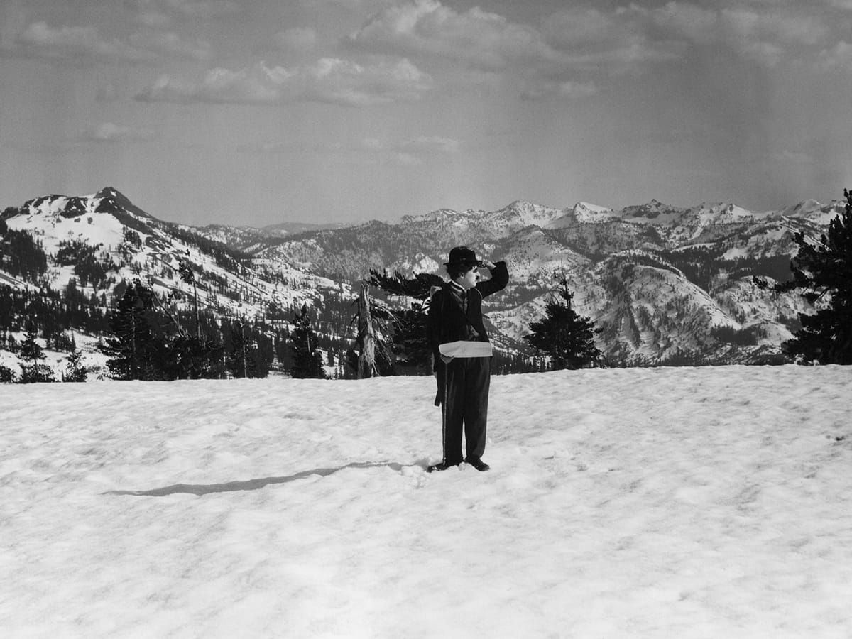 Charlie Chaplin in the Gold Rush standing in the middle of the snow atop the mountains