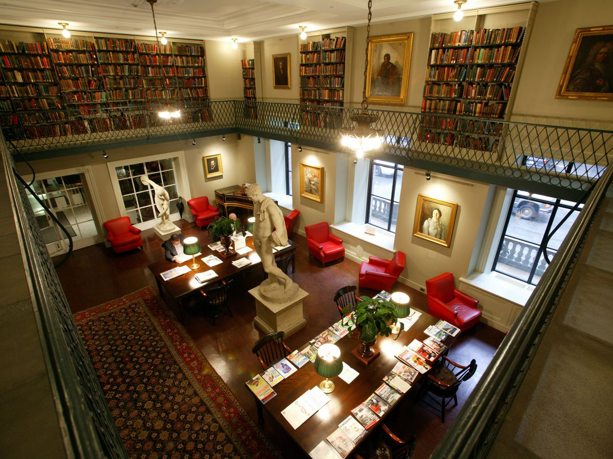 A cavernous reading room with an open upper level visible via balconies, and tables and chairs on the lower level's floor.