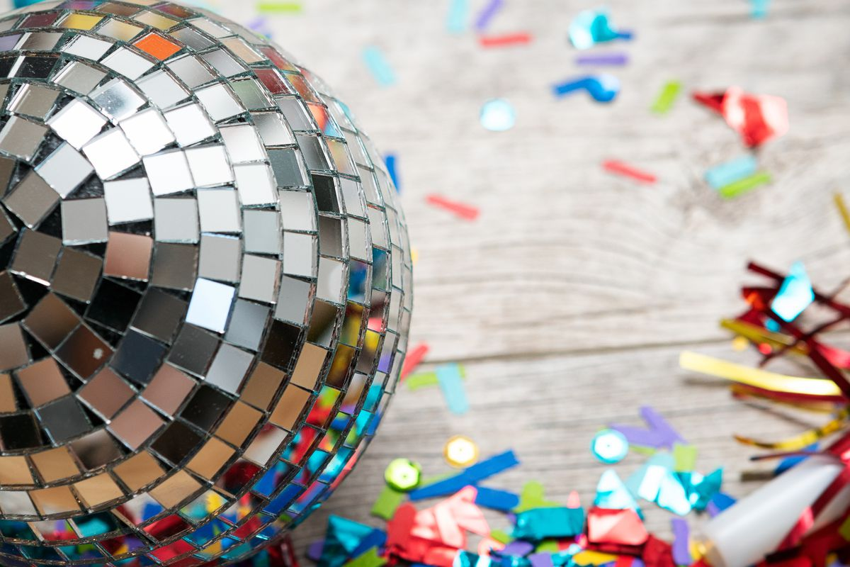 A disco ball on the ground with a pile of colorful confetti