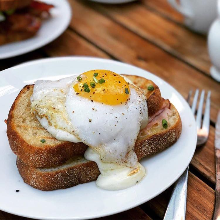 A very runny egg topped croque madame, on a plate beside a fork on a wooden patio table