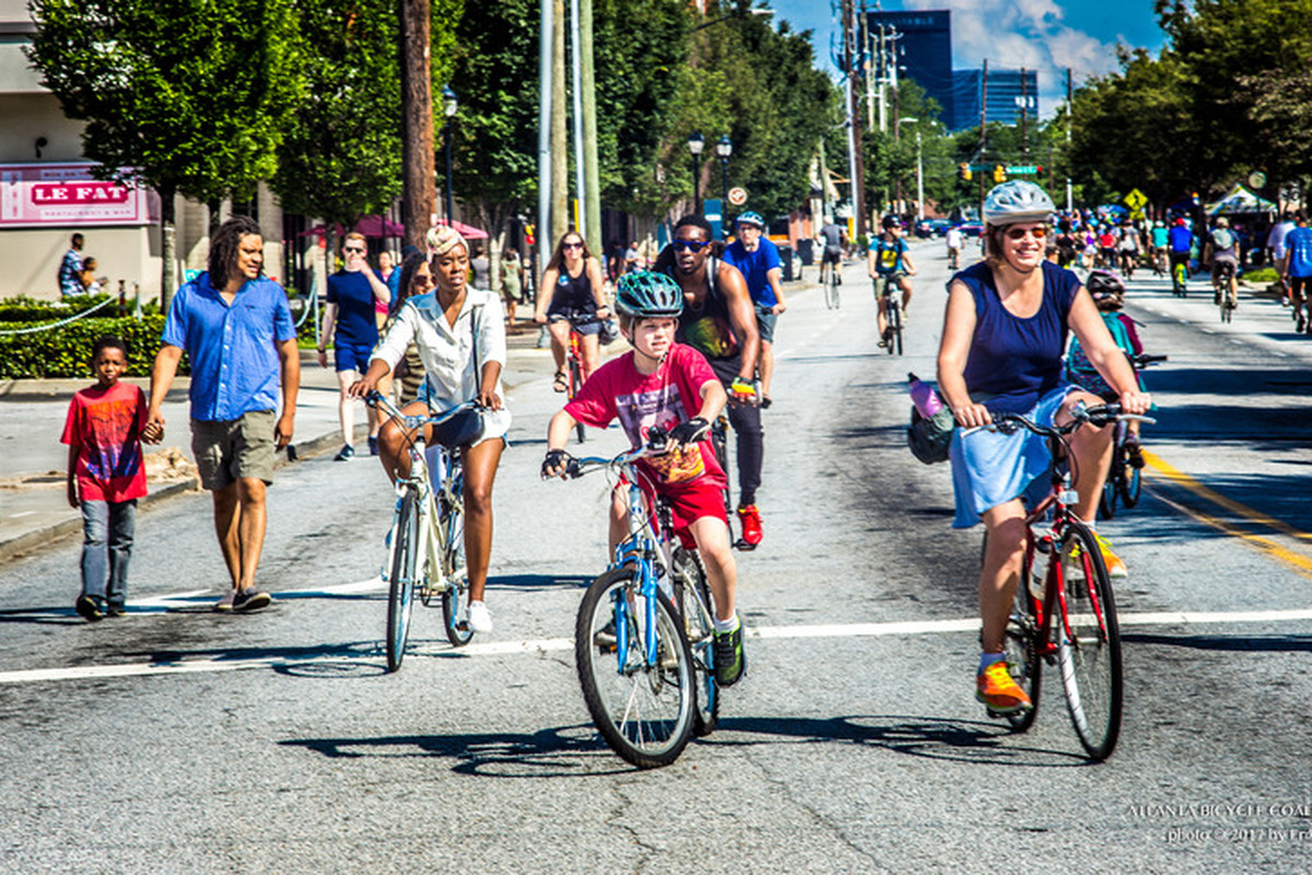 A picture of people biking on a crowded howell mill road.