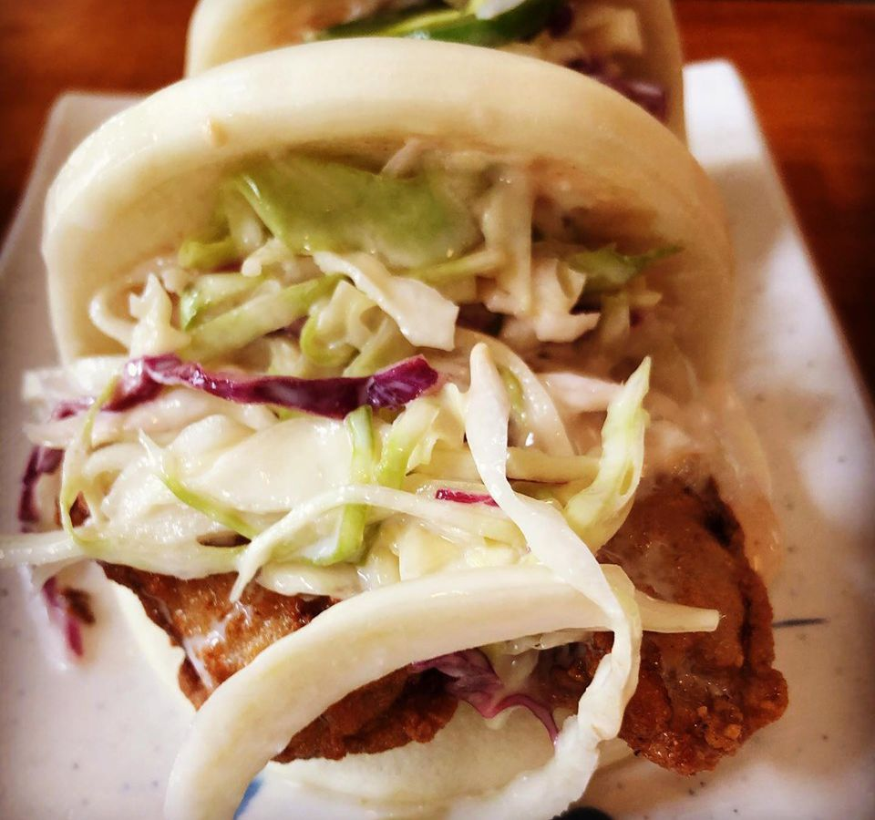 A steamed bun filled with fried oysters, coleslaw, and aioli