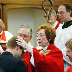 Bishop Carolyn Tanner Irish confirms John Carl Lair at St. Paul's Episcopal Church this past Sunday. Known for her tremendous energy, the bishop often gets up by 4 a.m. and begins her day with prayer and studying.