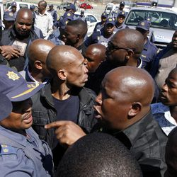 Firebrand politician Julius Malema, right argues with police officers, at Lonmin Platinum Mine near Rustenburg, South Africa, Monday, Sept. 17, 2012. London-registered Lonmin PLC announced it is halting construction of a new shaft, putting 1,200 people out of work, as the bloody and bitter strike at its beleaguered South African platinum mine dragged on its fifth week. The strikes that have halted work at seven gold and platinum mines have spread to the chrome sector, according to the official South African Press Association. Meanwhile, police blocked rabblerousing politician Julius Malema from addressing some 3,000 strikers gathered at a stadium at the Lonmin mine at Marikana, northwest of Johannesburg.