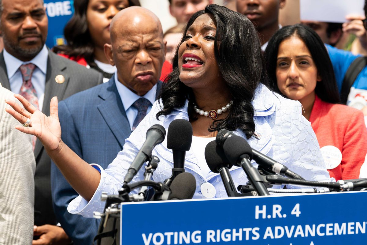 Representative Terri Sewell speaks in front of microphones flanked by Congress members outside Capitol building.
