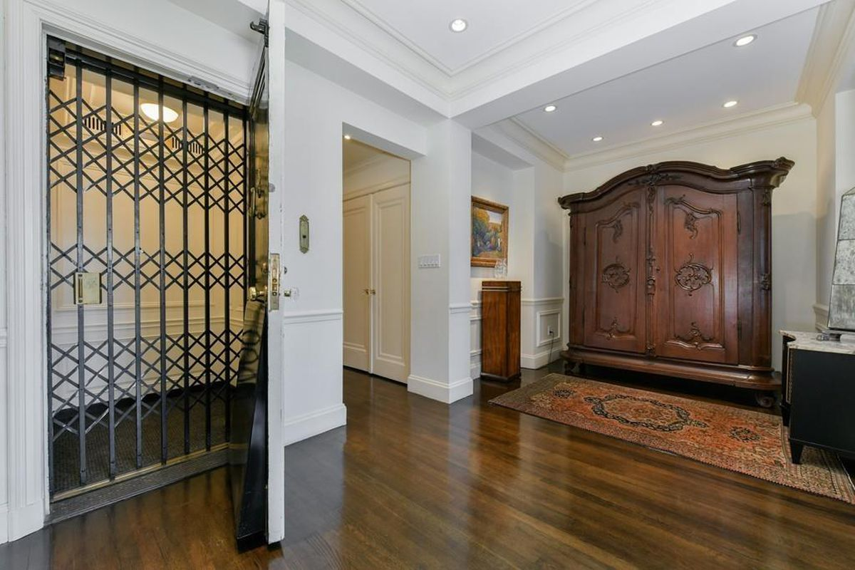 A condo foyer via an elevator, and the cage-like door of the elevator is closed.