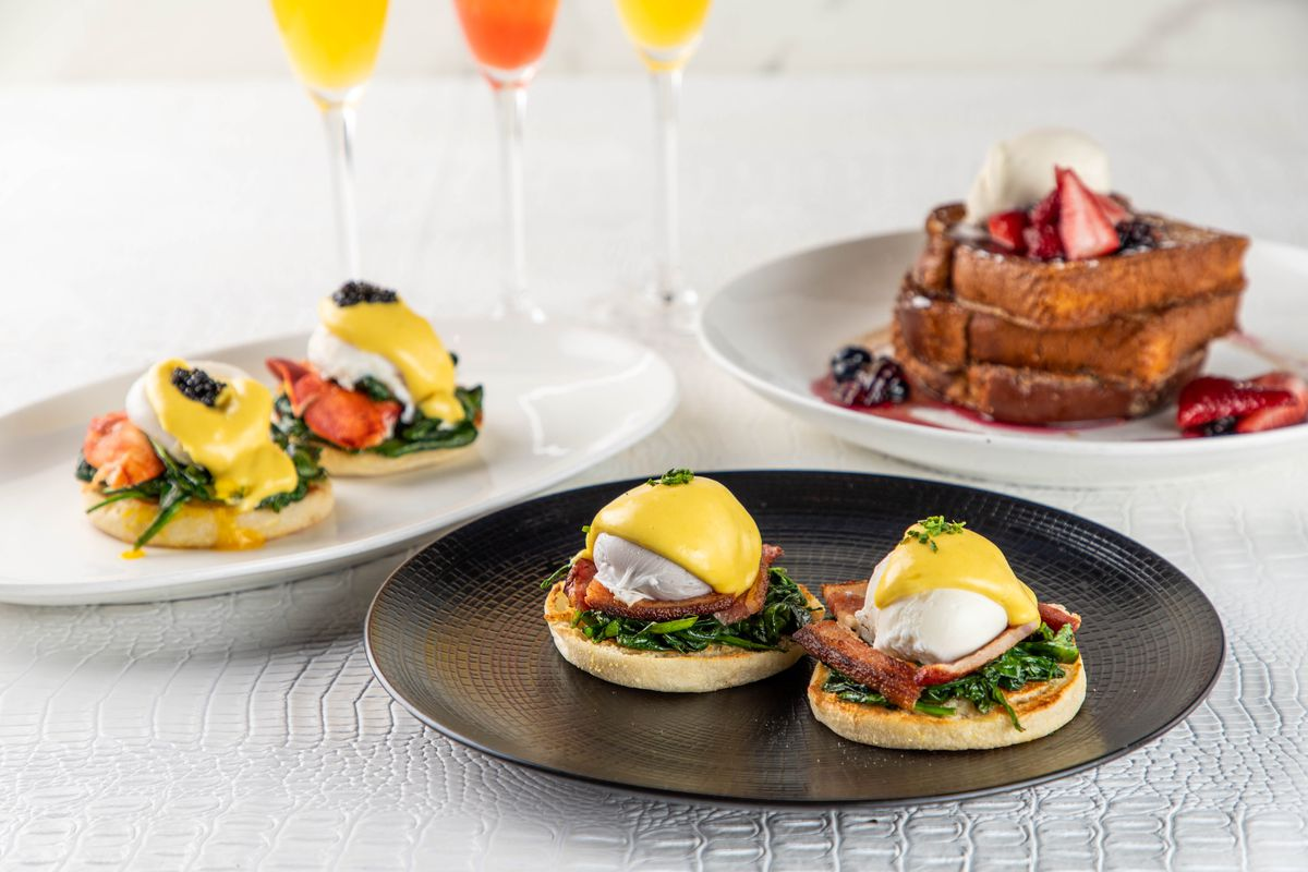 Two plates with eggs Benedict and another plate of waffles