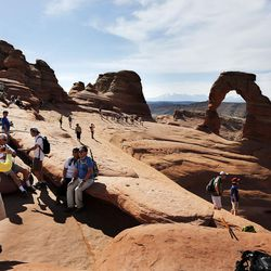 Tourists gather at Delicate Arch in Arches National Park near Moab on Friday, June 3, 2016.