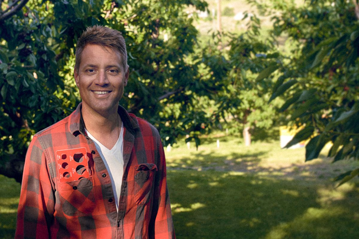 Eight Row chef David Nichols on his family's orchard in Wenatchee, WA, with trees and greenery in the background.