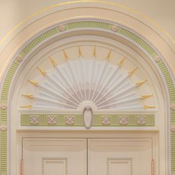 A detailed arched door casing of the celestial room in the Mesa Arizona Temple shows off the Colonial Revival style, popular in 1920s America, that includes fluting, rosettes, cartouches, and egg and dart motifs, accented with gold leaf.