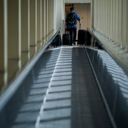 A traveler disembarks a moving walkway at Salt Lake City International Airport on Thursday, April 30, 2020. Like airports all over the world, Salt Lake's airport has seen air traffic plummet due to the COVID-19 pandemic.