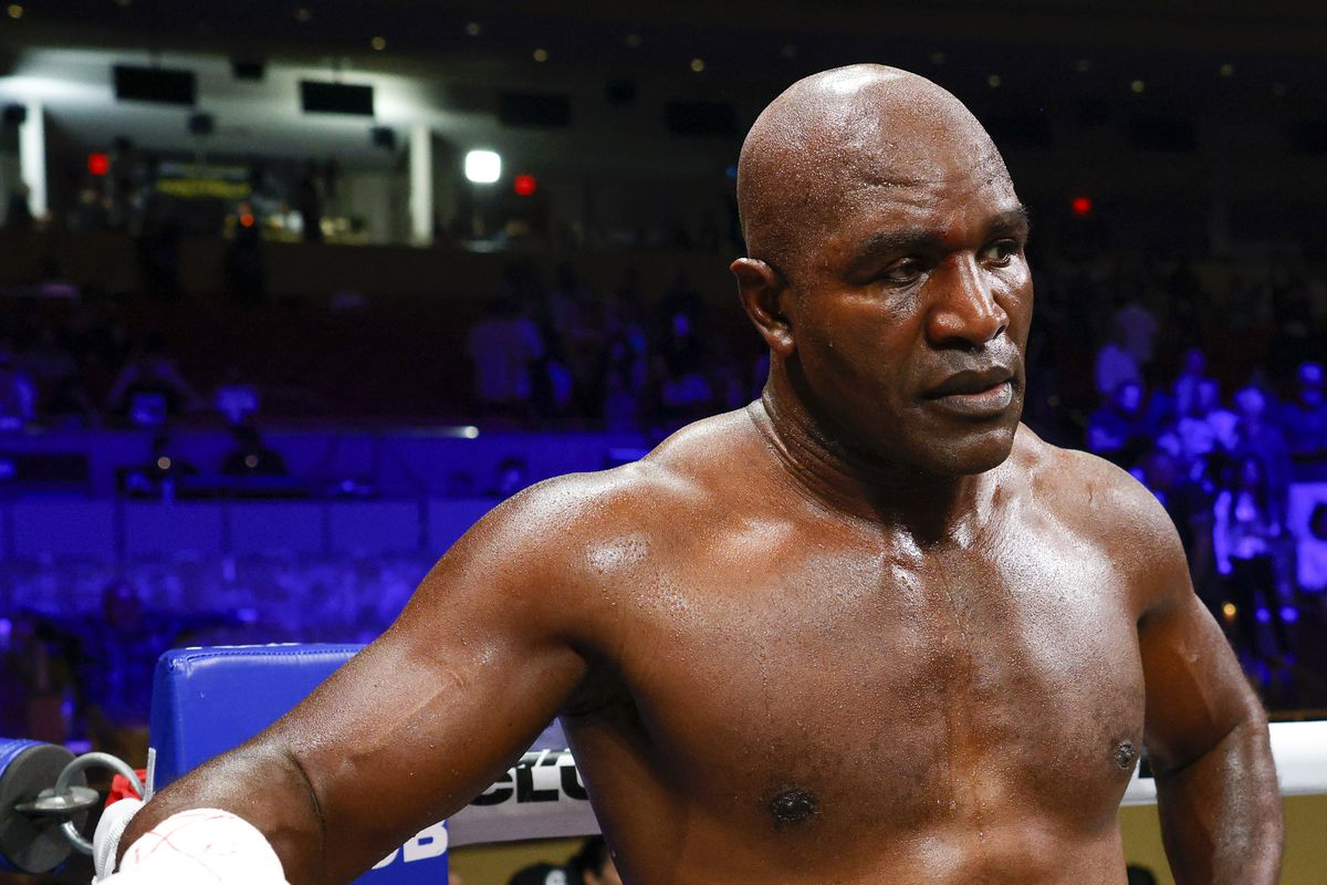 Evander Holyfield looks on as Vitor Belfort celebrates his victory in their Triller PPV boxing match.