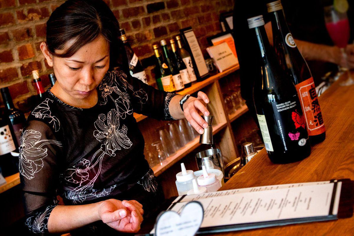 Yoshiko Sakuma pours a liquid into a cocktail shaker