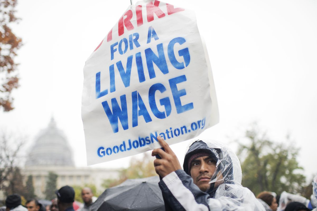 On the day of a Republican presidential debate, striking workers attend a rally in Upper Senate Park with Sen. Bernie Sanders, I-Vt., to call for a minimum wage of $15 per hour, November 5, 2015. Many of the low-wage workers hold jobs on Capitol Hill.