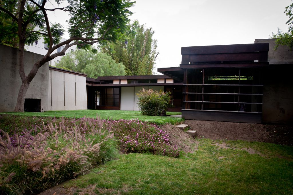 The exterior of the Schindler House. The facade is white with a dark brown roof. There is a lawn and flowers in the foreground.