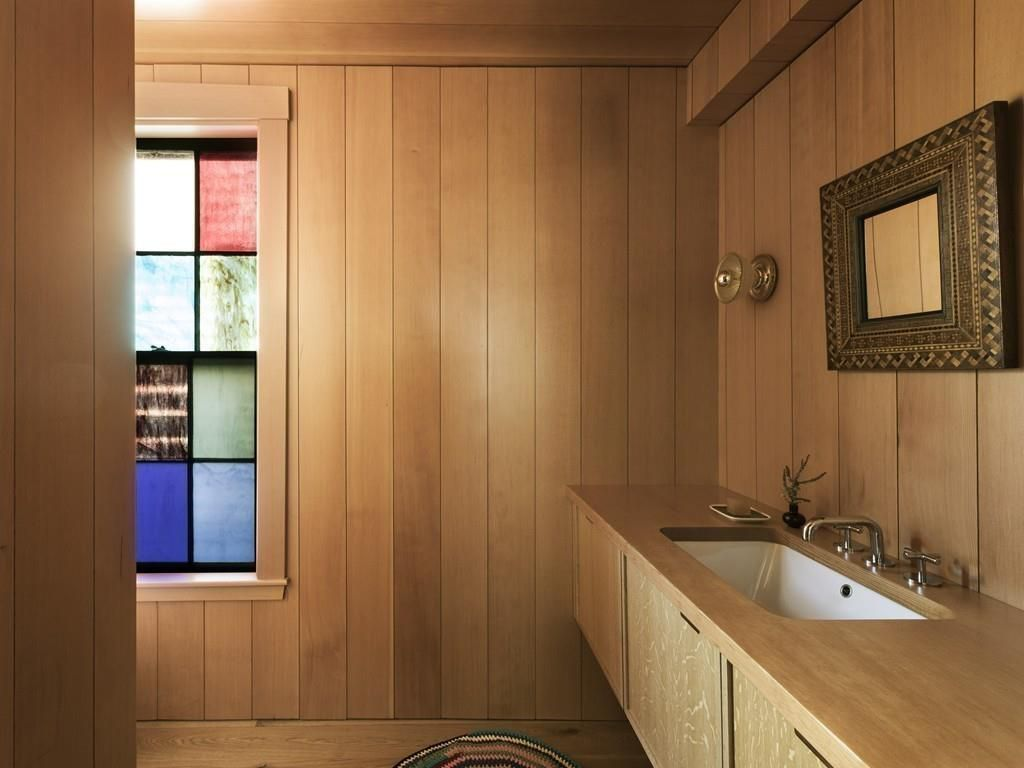 A wood-covered bathroom vanity with a multi-color window at the end.