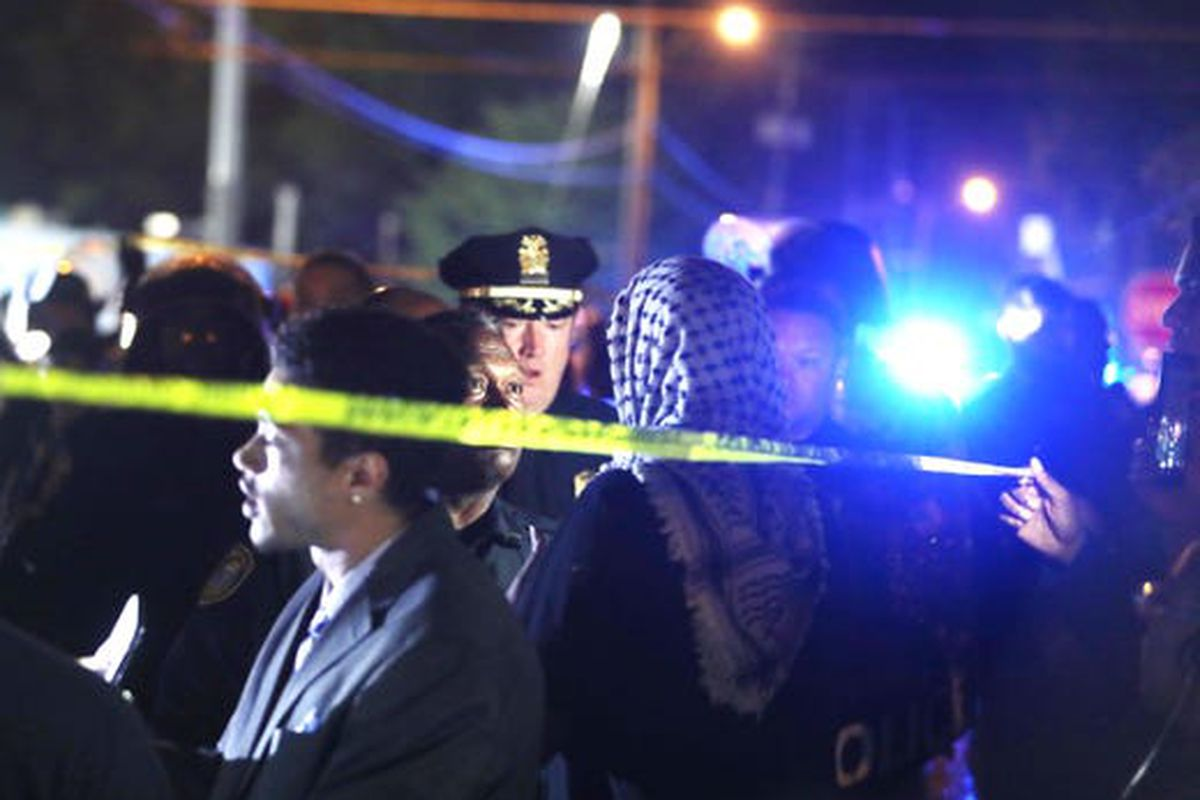 Memphis police officers talk with people following a fatal shooting involving U.S. Marshals in Frayser on Wednesday.