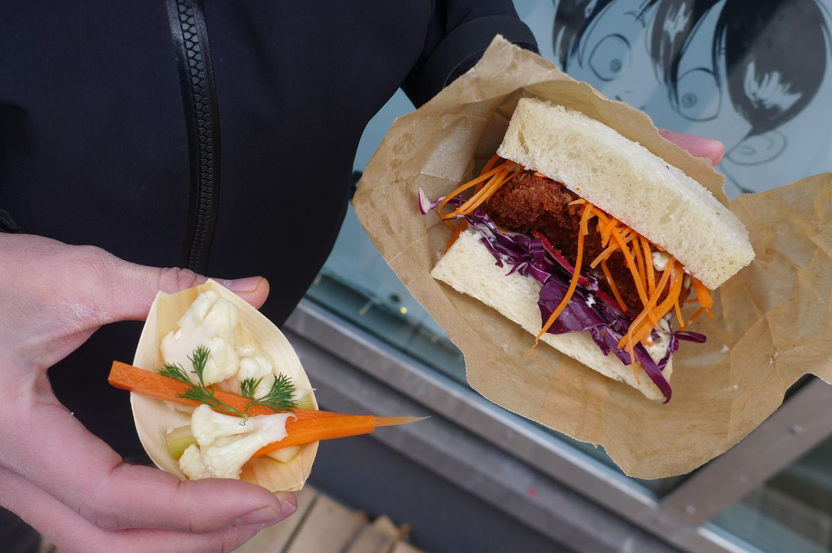 A hand holds a cutlet sandwich with mayo slaw sticking out while the other hand holds a small bamboo container of pickles while a cartoon figure looks on from a wall behind.