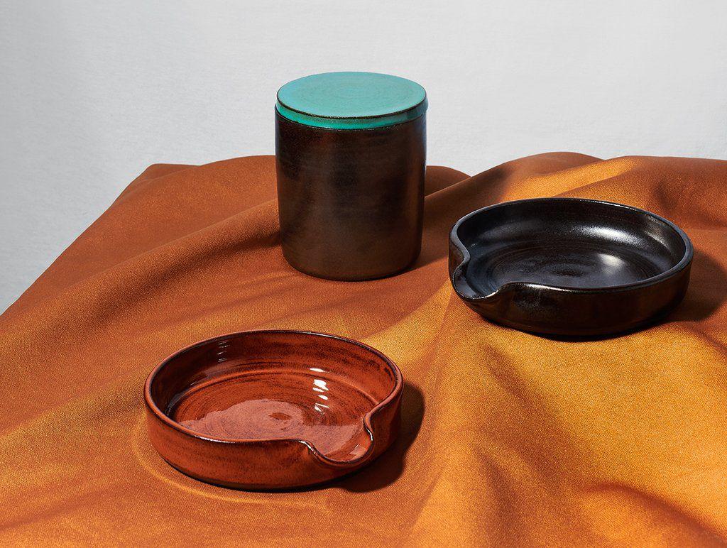 Ceniceros y accesorios para fumar sobre una pieza de tela naranja