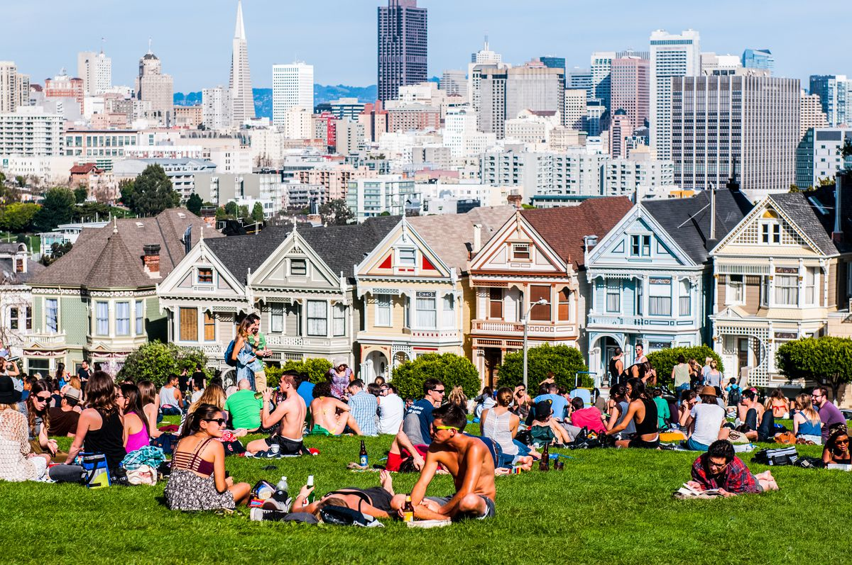 Residents enjoy a sunny day in Alamo Square park in San Francisco, with a view of the painted ladies Victorian homes and the city skyline in the background.