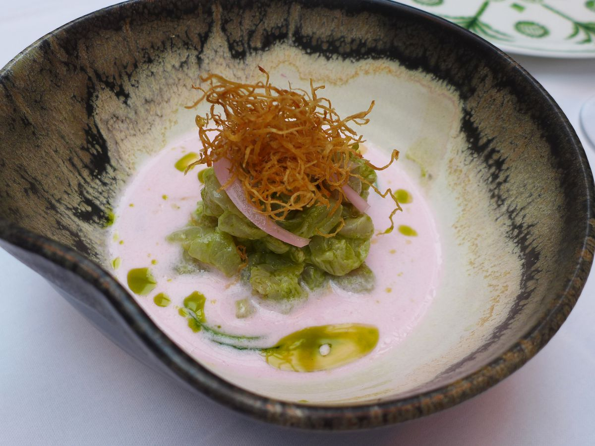 An asymmetrical streaky bowl with a creamy pink fluid and hillock of grayish diced fish.