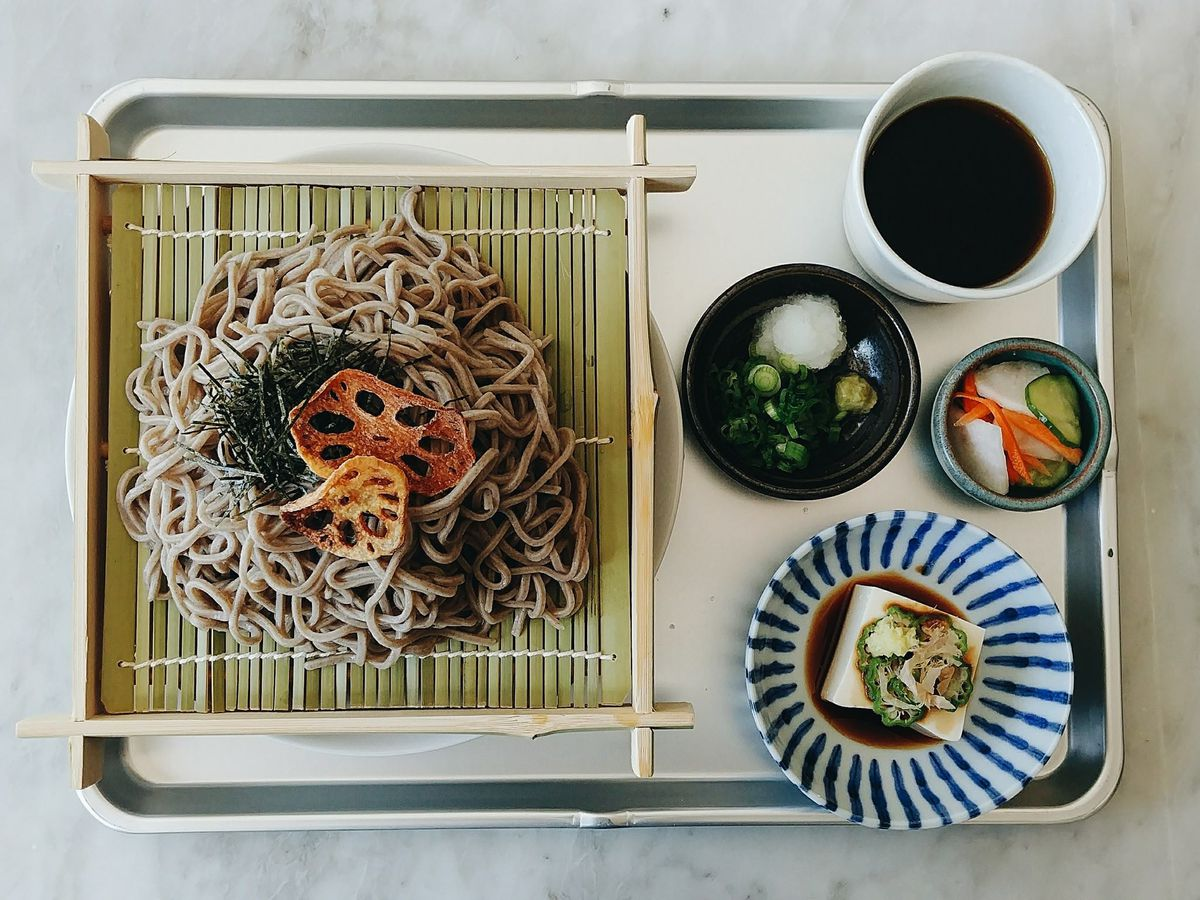 A platter of soba noodles with small garnish bowls on the side.