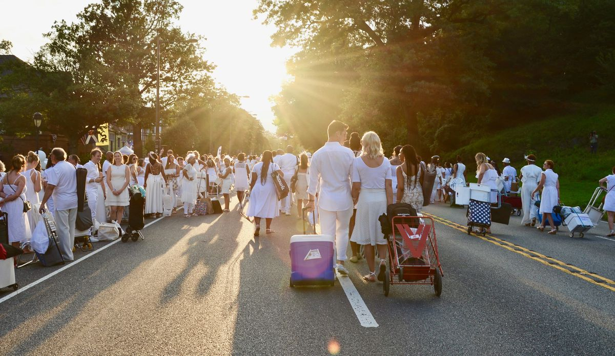 people dressed in white carrying picnic supplies up a street