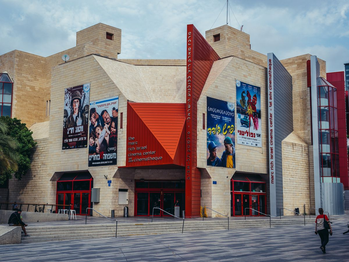The Tel Aviv Cinematheque. The facade is tan with a red entrance area.