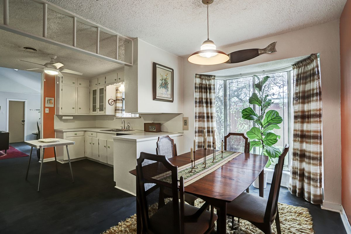 A dining room off of the white kitchen features a bay window with striped curtains and a four-person wooden table.