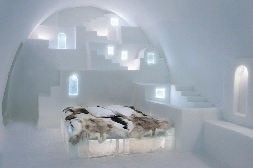 A series of steps are carved out of ice. A bed on top of ice sits at the base.
