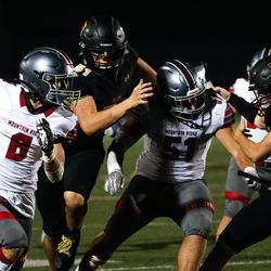 Mountain Ridge's Zander Hererra, left, goes for a touchdown through Wasatch's defense during the fourth quarter of a high school football game on Friday, Aug. 27, 2021, at Wasatch High School in Heber City. Mountain Ridge won 40-30.