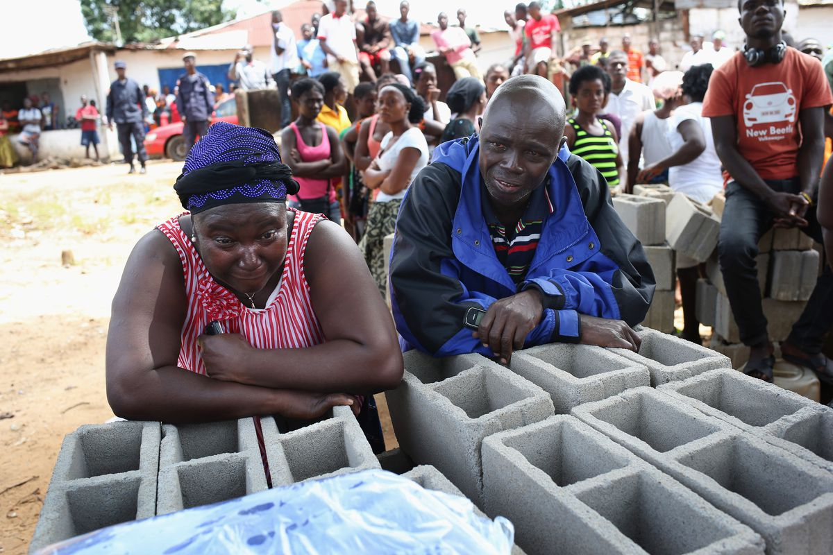 Relatives weep as a Liberian health department burial team prepares to enter the home of a woman suspected of dying of the Ebola virus. Some say these desperate times should not call for desperate measures.