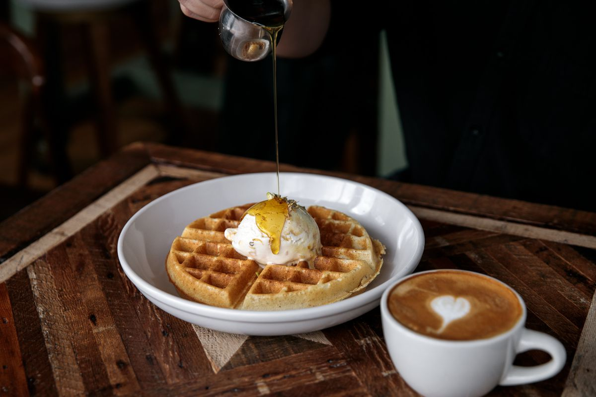 Syrup drizzles onto a scoop of butter on a belgian waffle at Folk next to a latte.