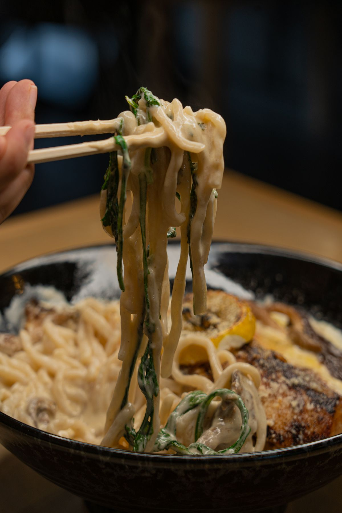 A pair of chopsticks tugs at a bowl of creamy noodles and greens