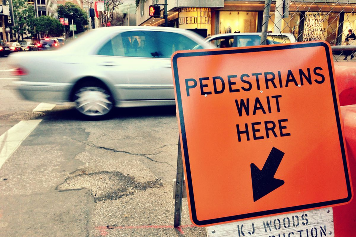 An orange sign on a street corner indicating where pedestrians should cross near a construction zone, as a car passes.