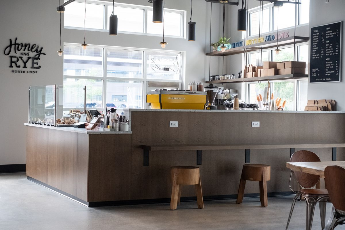 The view of Honey & Rye with a bar alongside it, a counter, and bright yellow espresso machine