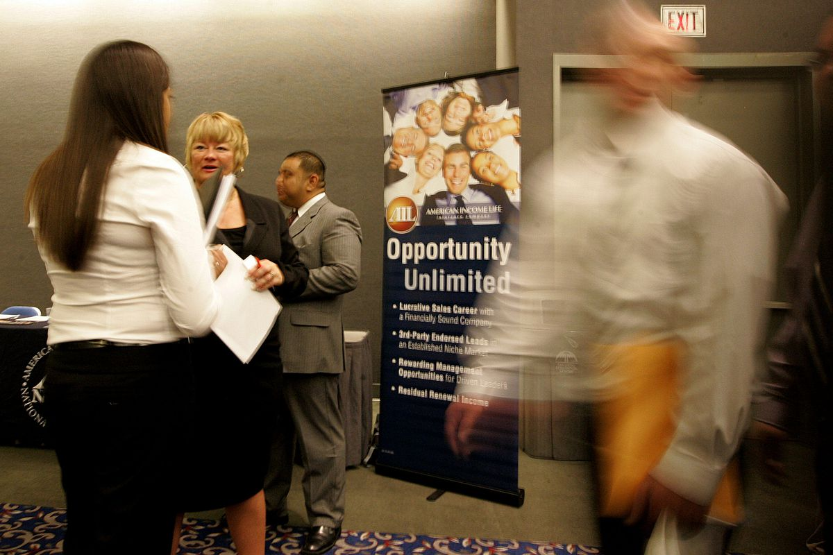 Job searchers interview with company representitives during a career fair at the Convention Center on February 5, 2010in San Diego, California