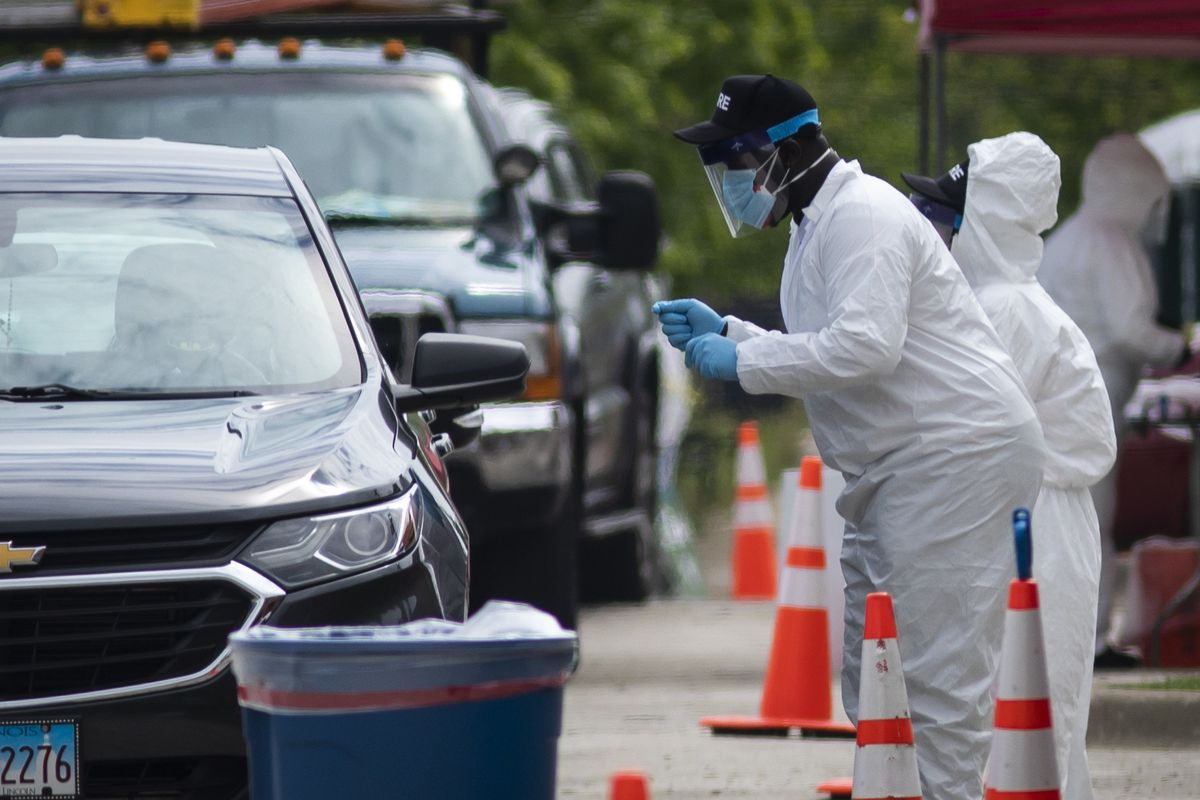 Workers collect coronavirus test samples at a drive-thru testing site Monday at Dr. Jorge Prieto Math and Science Academy on the Northwest Side.
