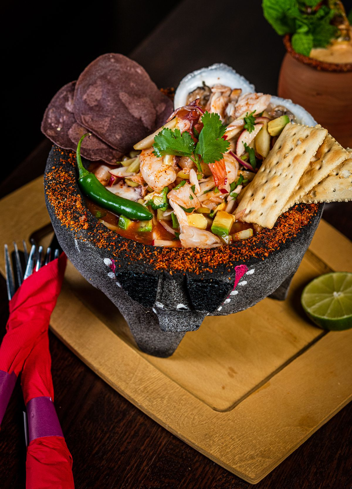 A molcajete at Anafre full of Sinaloan-style vuelve a la vida ceviche with crab, oyster, and octopus in a spicy seafood sauce