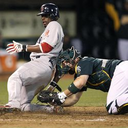Boston Red Sox' Pedro Ciriaco (77) slides safely into home plate past the tag of Oakland Athletics catcher Derek Norris (36) in the sixth inning of a baseball game Saturday,  Sept. 1, 2012 in Oakland, Calif.