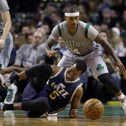 Utah Jazz guard Rodney Hood (5) loses control of the ball and grabs his ankle as Boston Celtics guard Isaiah Thomas (4) defends during the second half of an NBA basketball game in Boston, Wednesday, March 4, 2015. The Celtics won 85-84. (AP Photo/Elise Amendola)