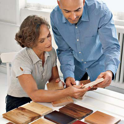 A Couple Looking At Hardwood Flooring Tiles