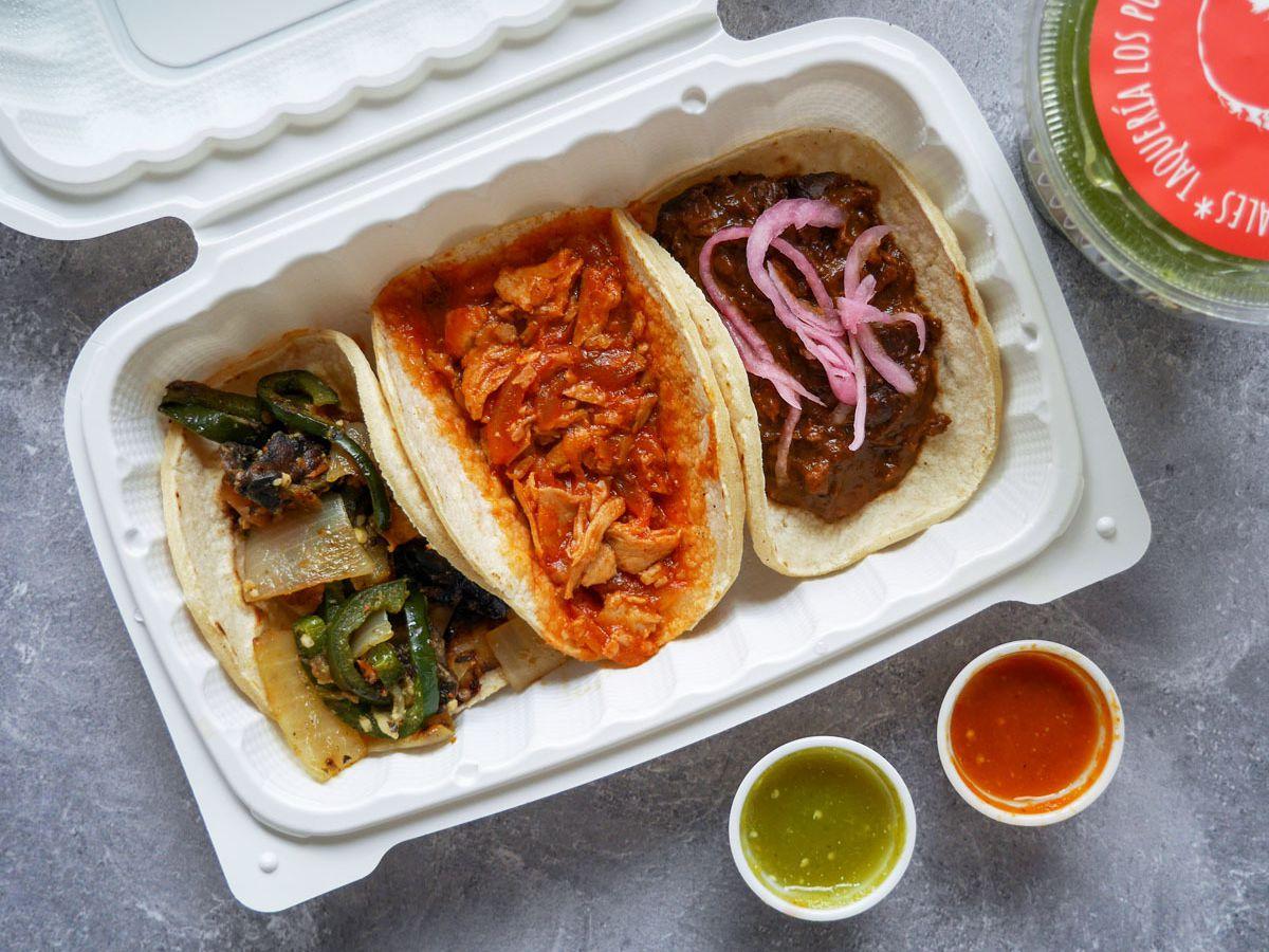 A photo of the el poblano, vegan tinga, and vegan mole tacos from Taquería Los Puñales